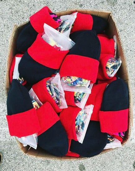 Box of children's hats filled with gloves and mittens.